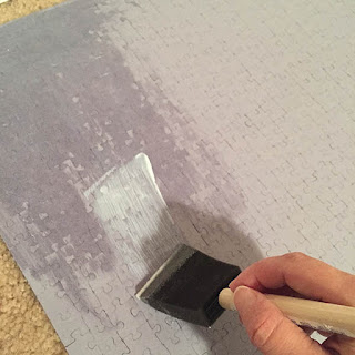 Foam brush applying glue to the back of a large puzzle