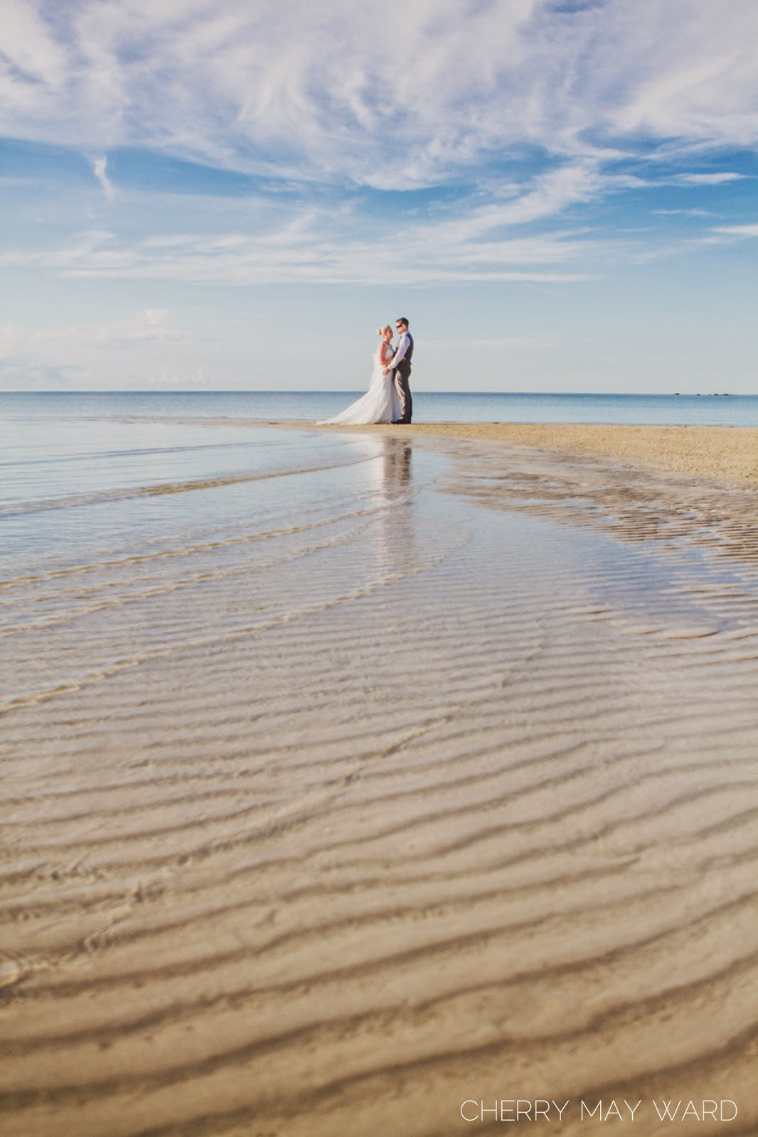 bride and groom standing on a sandbar in the distance, beautiful clear water with ripples in the sand on Koh Samui, Thailand trash the dress