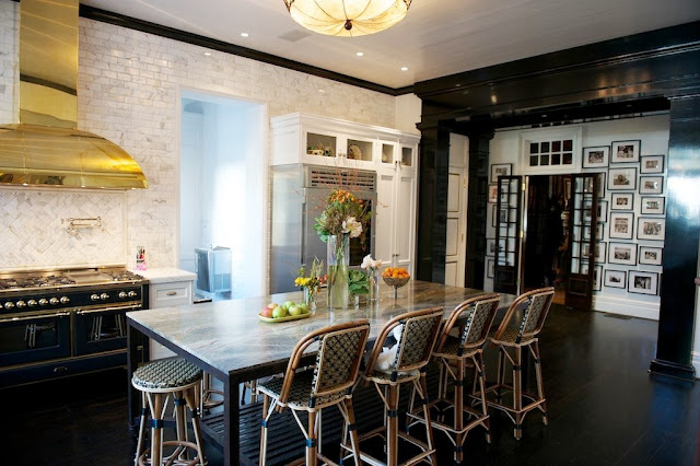 Kitchen with marble subway walls, white cabinets, dark wood floors, vintage light fixture over the island and Drucker's French Bistro barstools, an  ILVE Majestic stove with a bass hood and a black molded entry way