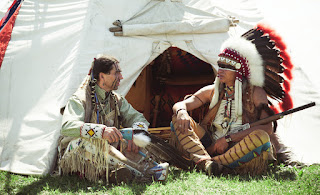 An Indian brave in war paint is seated next to the chief with headdress in front of a wigwam