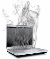 Picturer of a laptop computer with smoke rising from it