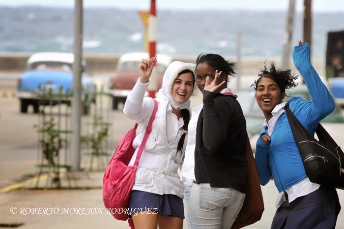 Jóvenes saludan mientras pasean bajo las temperaturas mínimas provocadas por el primer frente frio del año en La Habana, Cuba, el 7 de enero de 2014.