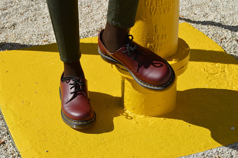 Fashion Blogger Anais Alexandre of Down to Stars in a vegan leather red doc martens by a fire hydrant.