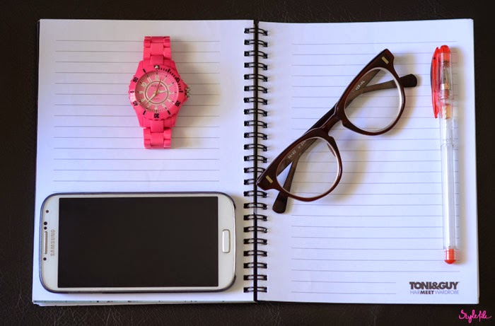 On a single ruled black notebook by Toni & Guy lies a pink zaza wrist watch, a samsung mobile phone, a red gel pen and thick cat eye framed spectacles