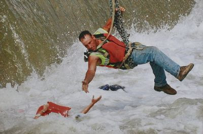 Image of man, suspended by chain, rescuing a person in danger of drowning near the spillway of a dam.