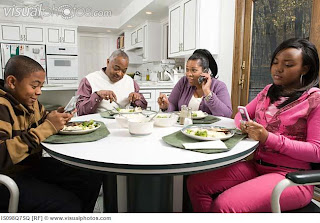family sitting at the table talking on the phone