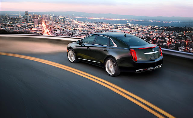 Black 2013 Cadillac XTS on curve above city at dusk