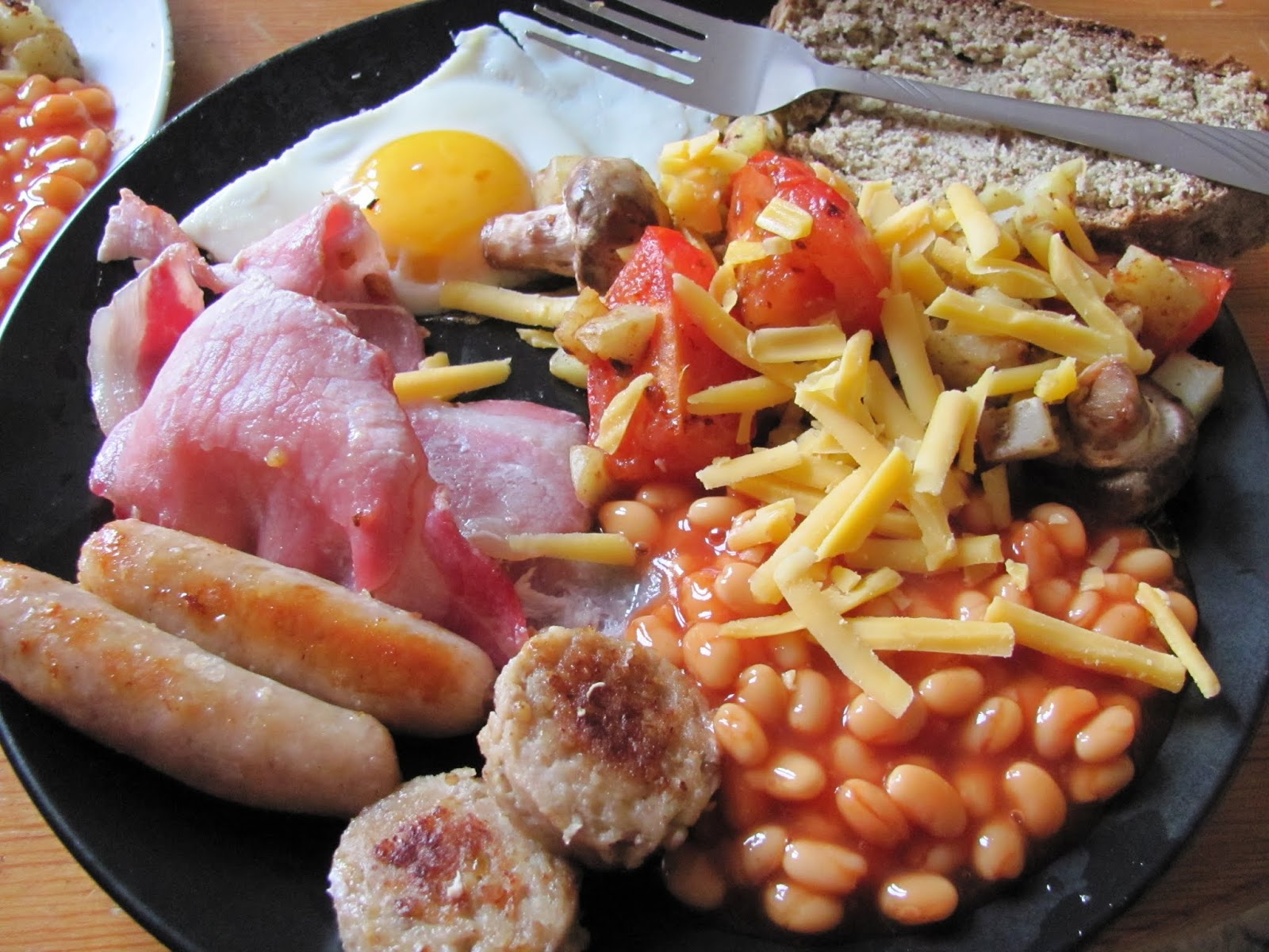 Closeup of Full Irish Breakfast featuring three meats, beans, vegetables, eggs, toast, and cheese