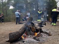 El foc per poder fer pa torrat i al fons, les botifarres