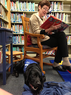 Kathleen reads a story in her rocking chair while Coach gnaws  his nylabone beside her in coat.
