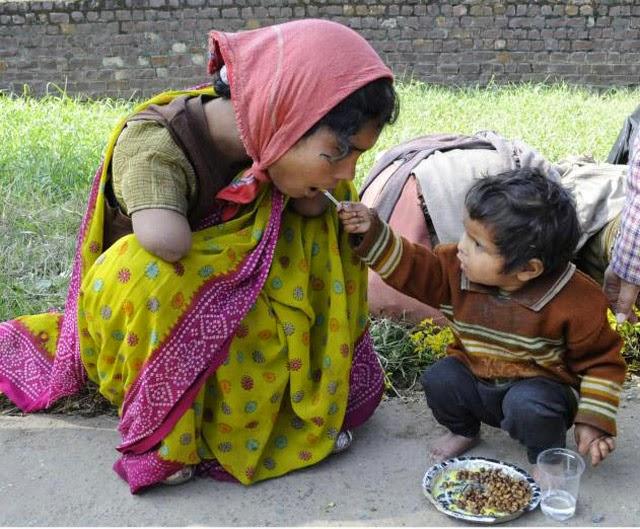 niño de dos años da de comer a su madre con discapacidad