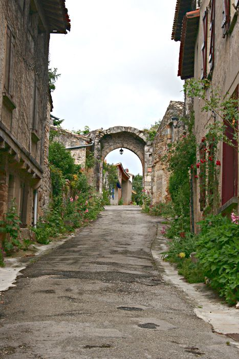 narrow uphill road with archway at the end