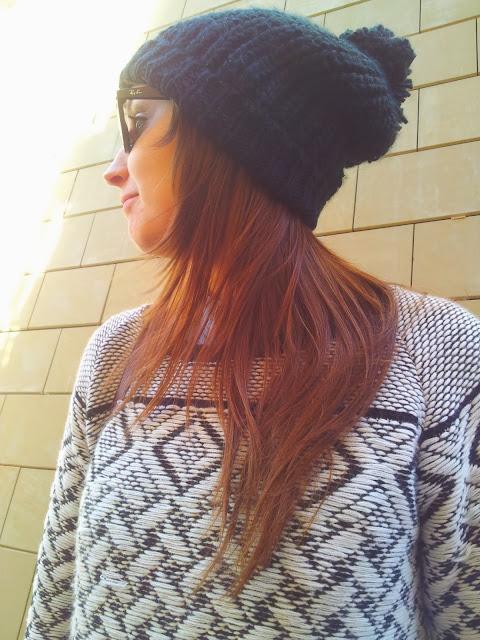 Jersey navideño en blanco y negro con gorro de lana negro de Zara y jeans de Stradivarius.