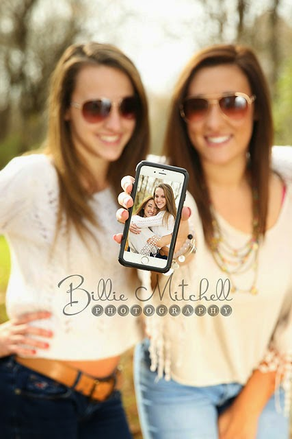 two teen girls standing side by side in sunglasses holding out a phone to the camera with their picture on it