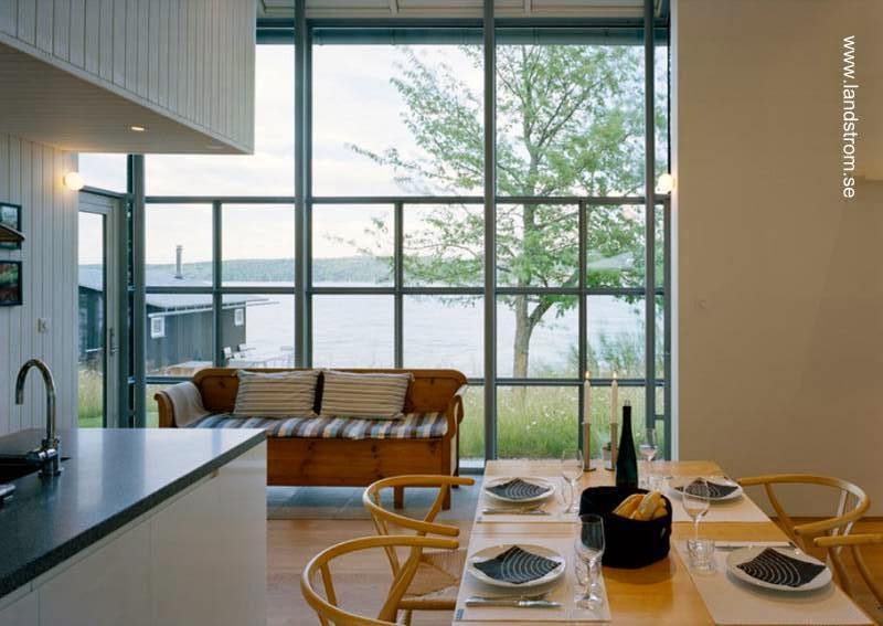 Interior del open plan cocina comedor y gran vidriera al exterior