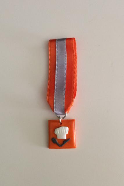 Foto de medalla cuadrada en naranja con un gorro de cocinero y cubiertos cruzadoss