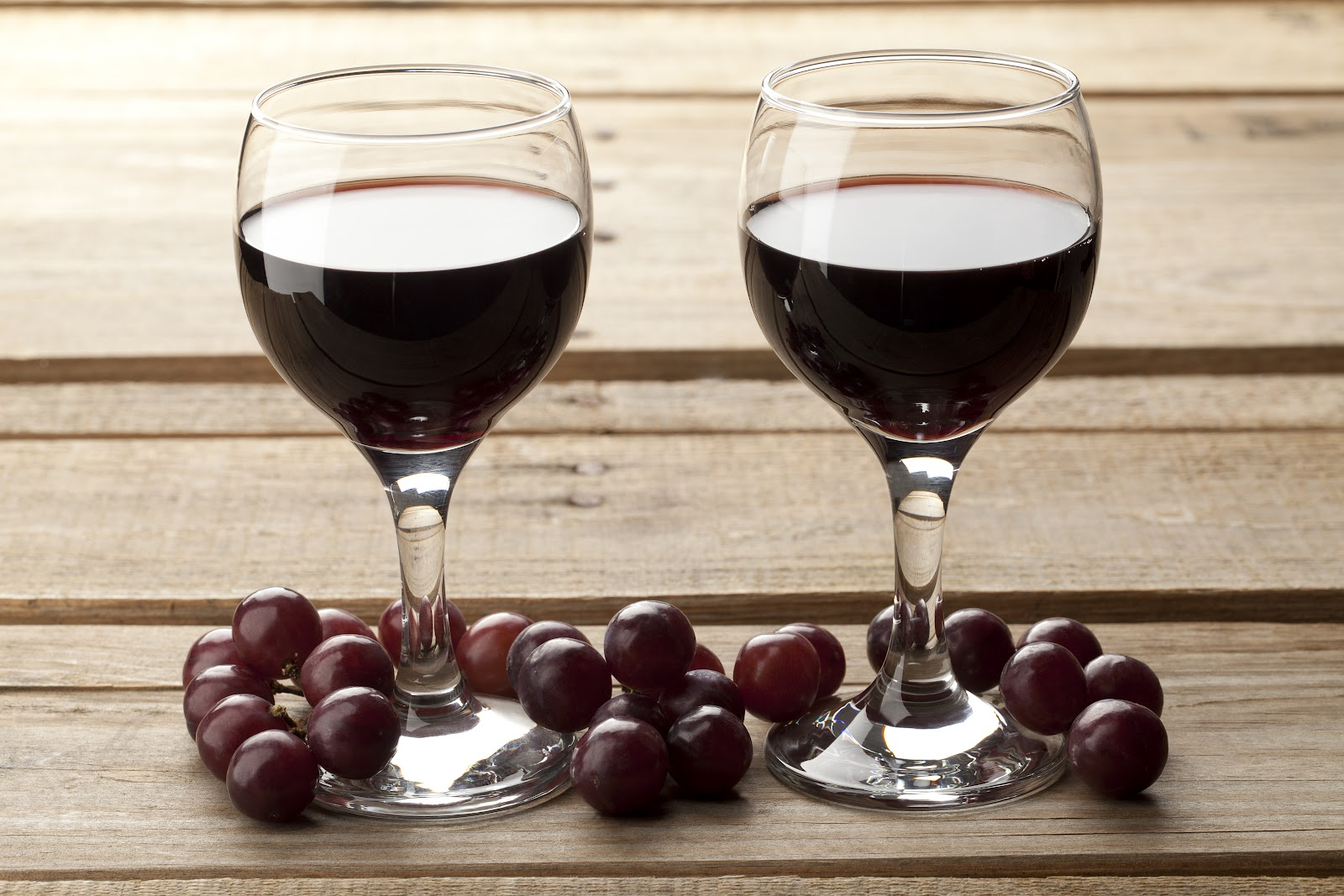 Image of pair of red wine with grapes place on wooden table