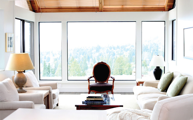 Vancouver apartment with white sofas with a hillside view of green evergreen trees