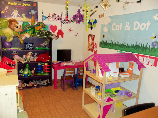 Playroom with bright colors, pink, purple, and big Kidkraft So Chic Dollhouse