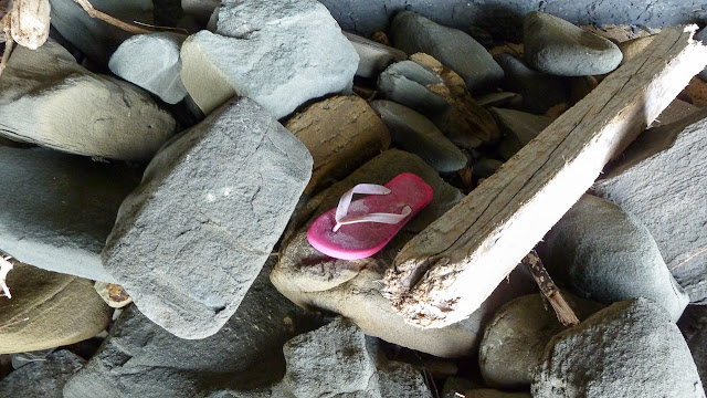 pink thong lying amongst rocks