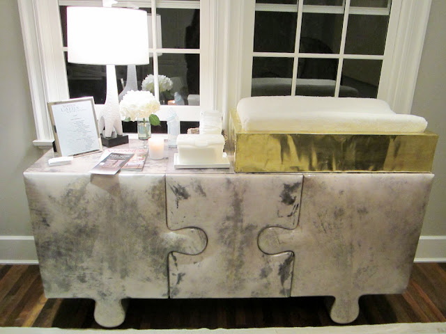Close up of the marbled side table made of three puzzle pieces. On the counter there is a gold baby changing station and a white lamp