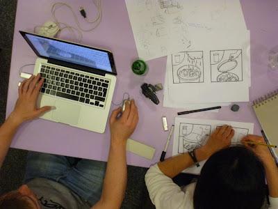 Vogelperspektive: An einem Tisch wird per Computer und Zeichenstift das Thema analysiert