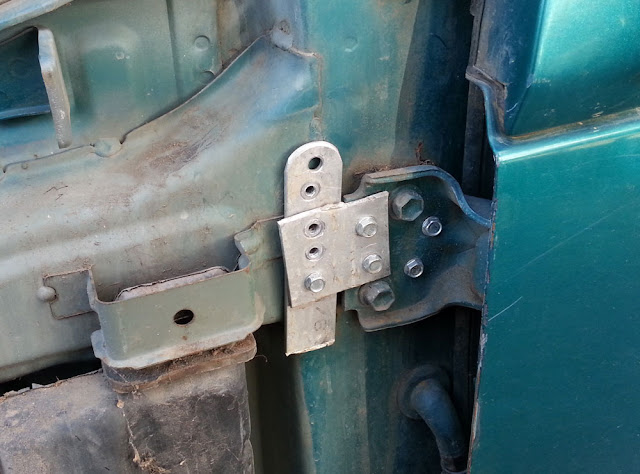 A half-assed fix to a bent door.