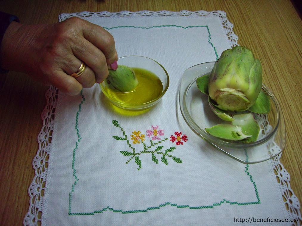 Mojando la hoja de la alcachofa en la mezcla de aceite, vinagre y sal