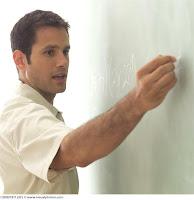 gay teacher writing on chalkboard