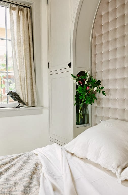 White bedroom with built in tufted headboard and fresh flowers