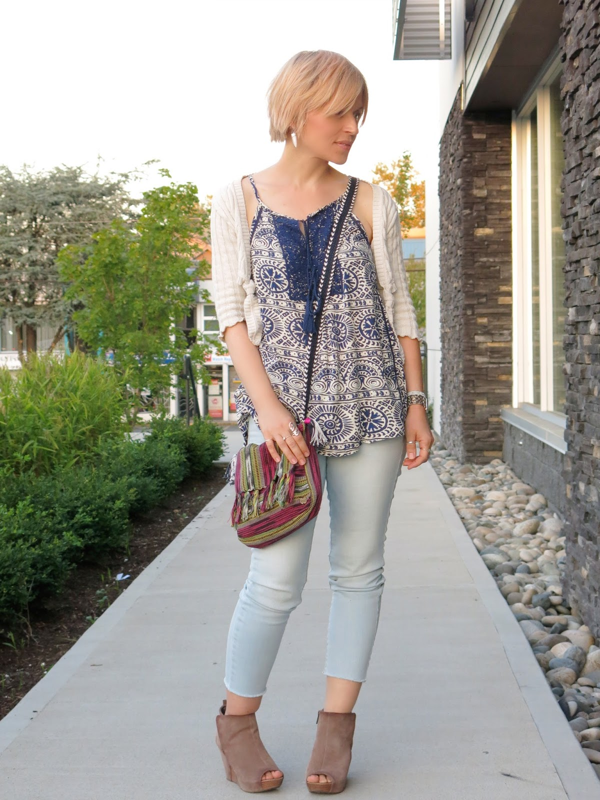 styling bleached skinny jeans with a peasant-style tank top and cable-knit shrug