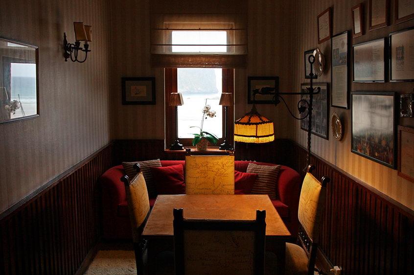 Sala com mobiliário requintado sob iluminação de luz quente. Janela para a praia com uma orquídea no parapeito