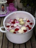 Семпла, но много ефектна романтична декорация от тенджера с плаващи свещи и розови листенца