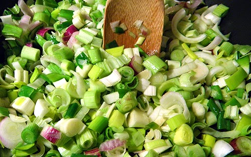 Closeup of Saute Pan Filled with Onions, Leeks, and Green Garlic