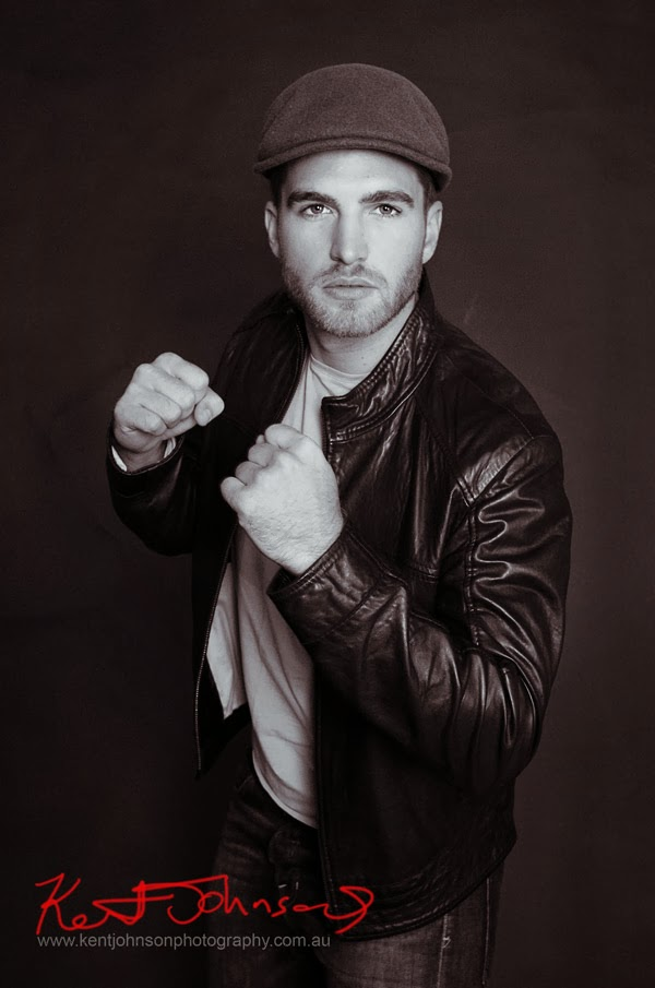 Male model portfolio shoot - Evan Shadow Boxing in leather jacket and driving cap. Black and white photograph on black background, photographed by Kent Johnson.