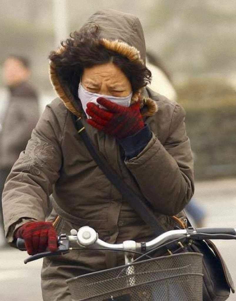 Mulher tenta se proteger em Pequim