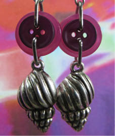 Cheeky Charm Earrings have silver seashells hanging from pink buttons