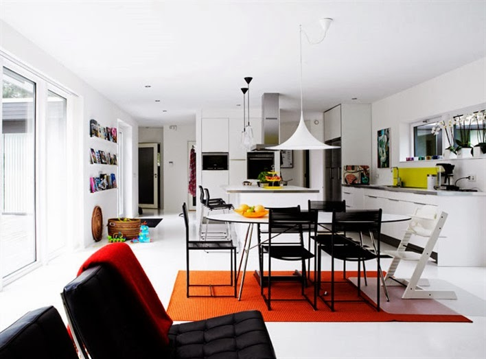 Modern open kitchen, living room and dining room with black Barcelona chairs
