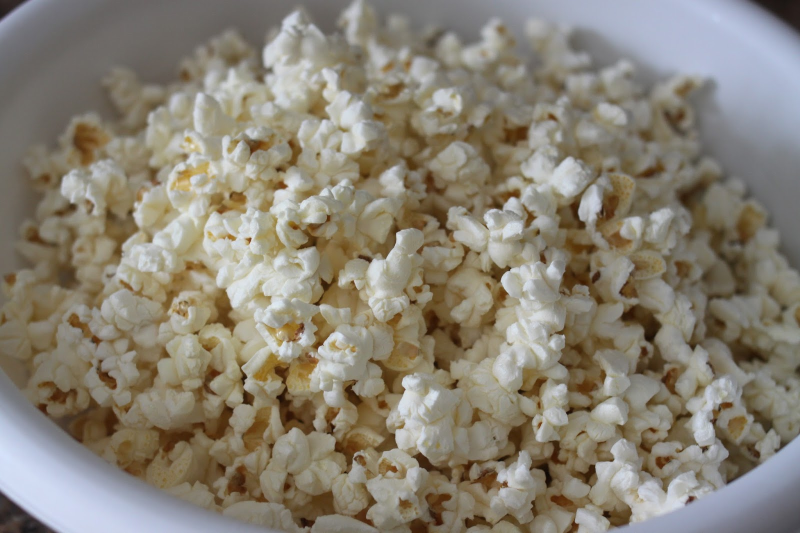 While your Popcorn is cooling, heat up your white chocolate/almond ...