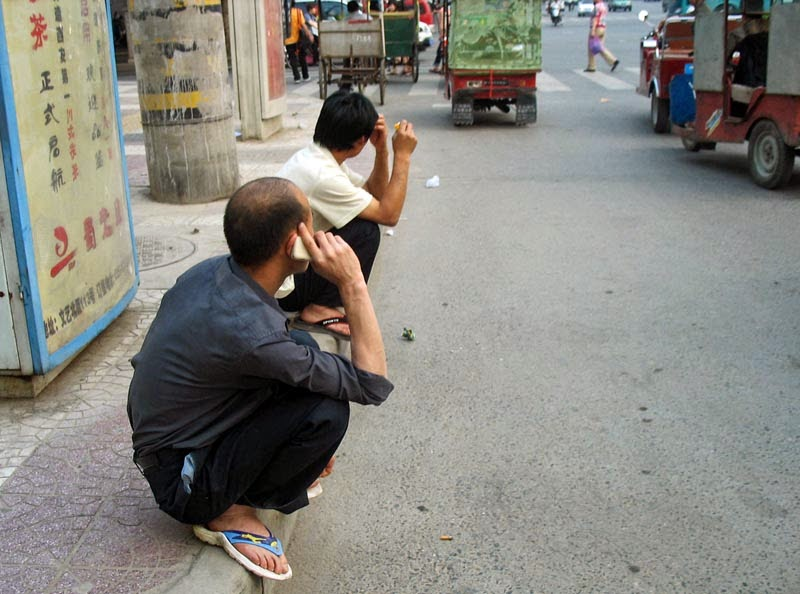 chinese men sitting on their haunches