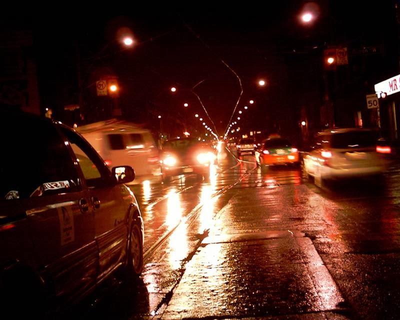 Una escena en el que se aprecia un taxi en la nocturna noche lluviosa