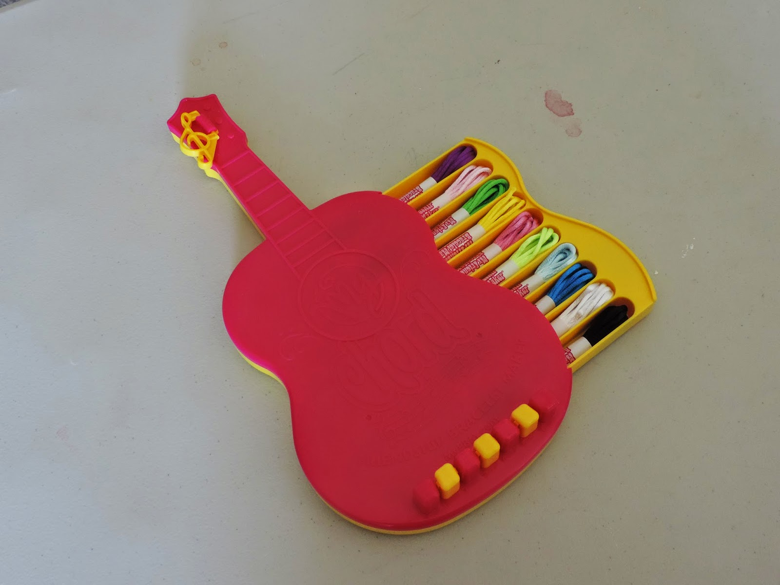The Guitar Shaped Kit Has A Drawer In The Side, Which Holds An Assortment  Of Colored Satin Cord