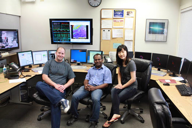 (From left:) University of Texas assistant professor Steven Finkelstein, Texas A&M postdoctoral researcher Vithal Tilvi and University of Texas graduate student Mimi Song, pictured in the observing room at W.M. Keck Observatory, where they spent two nights last April. The small monitors show what the group used to control MOSFIRE, while the large monitor on the left shows their view of the telescope operator. Finally, the one behind Finkelstein shows where the telescope is pointing as well as the current conditions. (Image courtesy of Steven Finkelstein.)