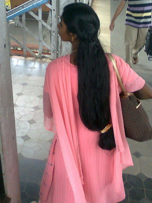 A Indian college girl with loose open long hair tied at end waiting at railway station
