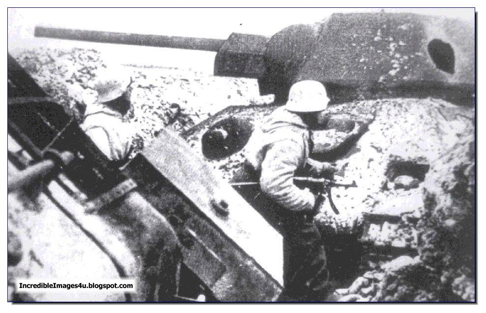 German soldiers move past a destroyed t 34 tank cautiously in october