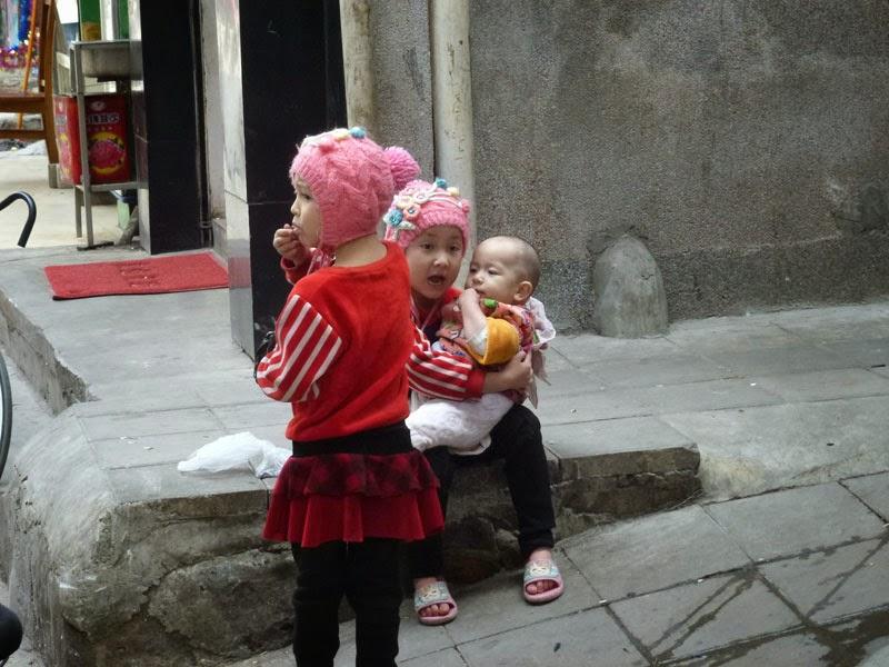 niñas cuidando hermano en el barrio musulmán