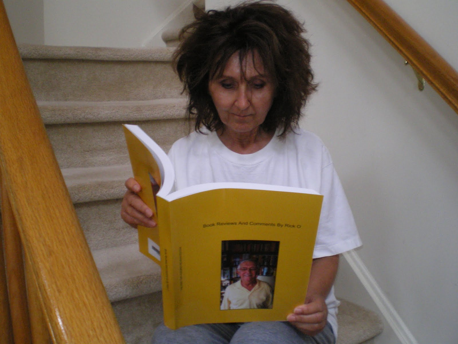 "Book review contributor, Pat Koelmel peruses her copy of ""Book Reviews and Comments by Rick O."""