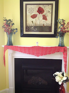 completed coral lace shawl displayed stretched across the fireplace mantel