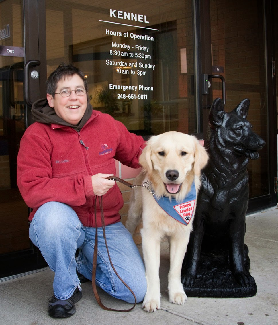 "A short-brown haired woman is kneeling on one knee next to a standing golden retriever. She is wearing a maroon fleece jacket and blue jeans. The dog has a blue bandana with a white triangle patch with red letters that say Future Leader Dog. On the right side is a black statue of a german shepherd dog. Behind them are glass doors with white letters that say ""Kennel"" with the hours underneath."