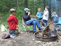 Kids interacting with an adult next to a campfire